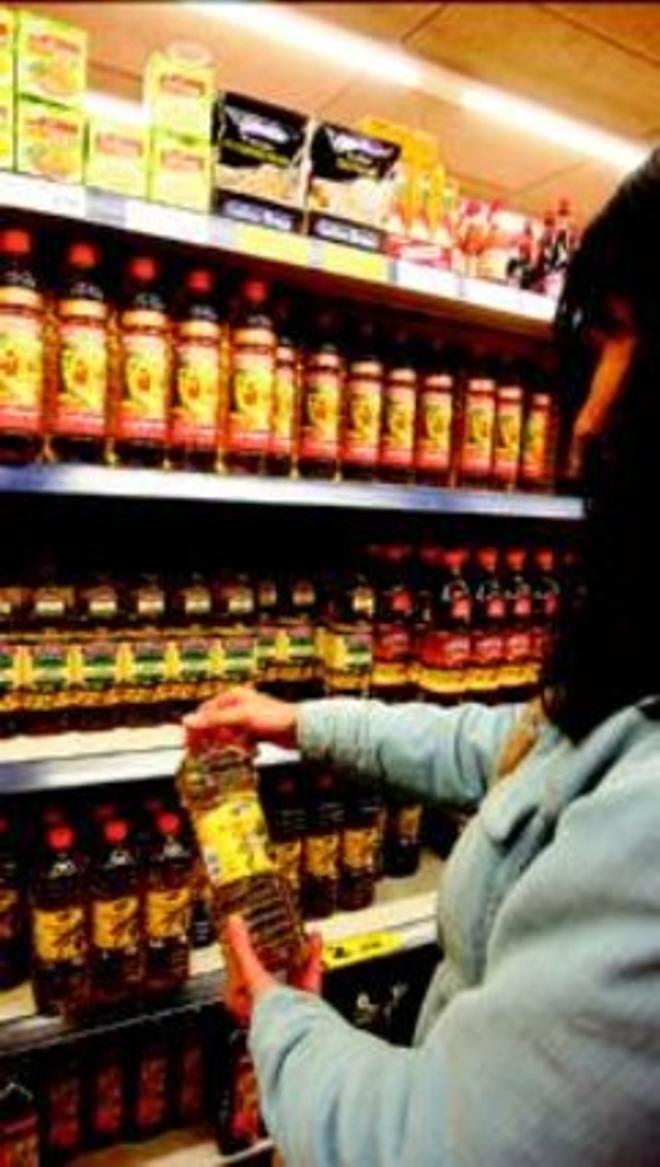 Una mujer observa las ofertas de aceite en un súper de Barcelona.