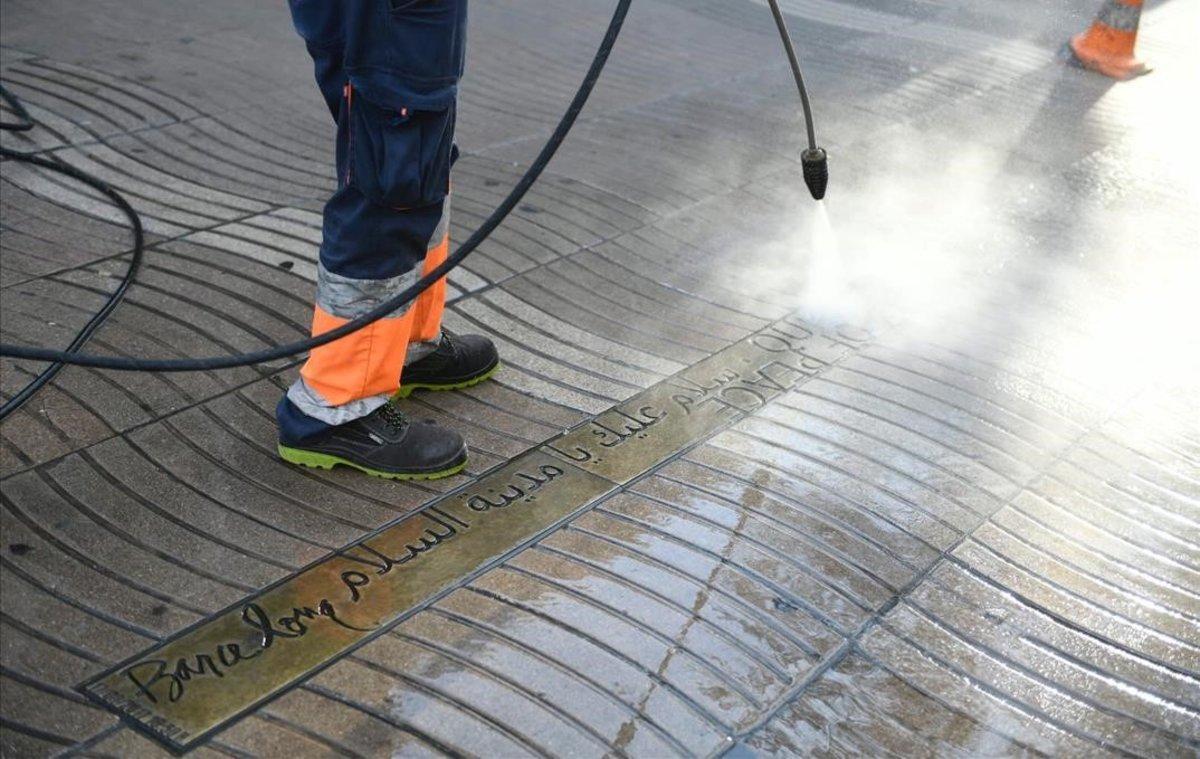 Un operario de limpieza del Ajuntament repasa el memorial del 17-A en la Rambla que ayer fue boicoteado con cemento.
