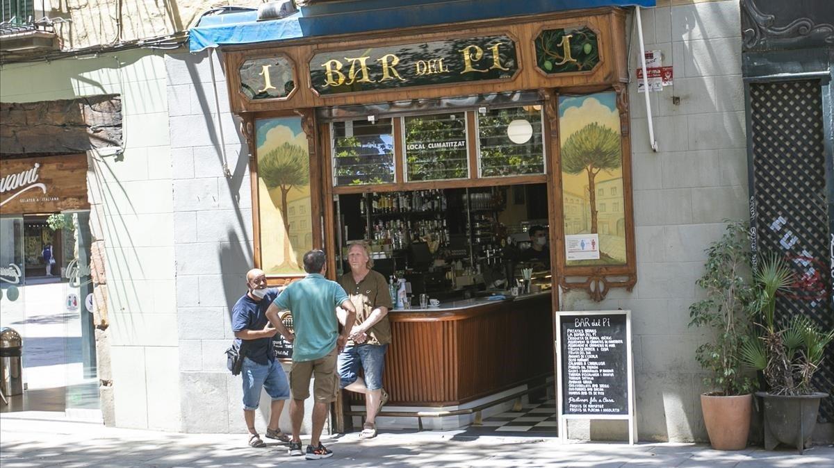 Unos ciudadanos charlan en la puerta del Bar del Pi, de la Plaça de Sant Josep Oriol de Barcelona.