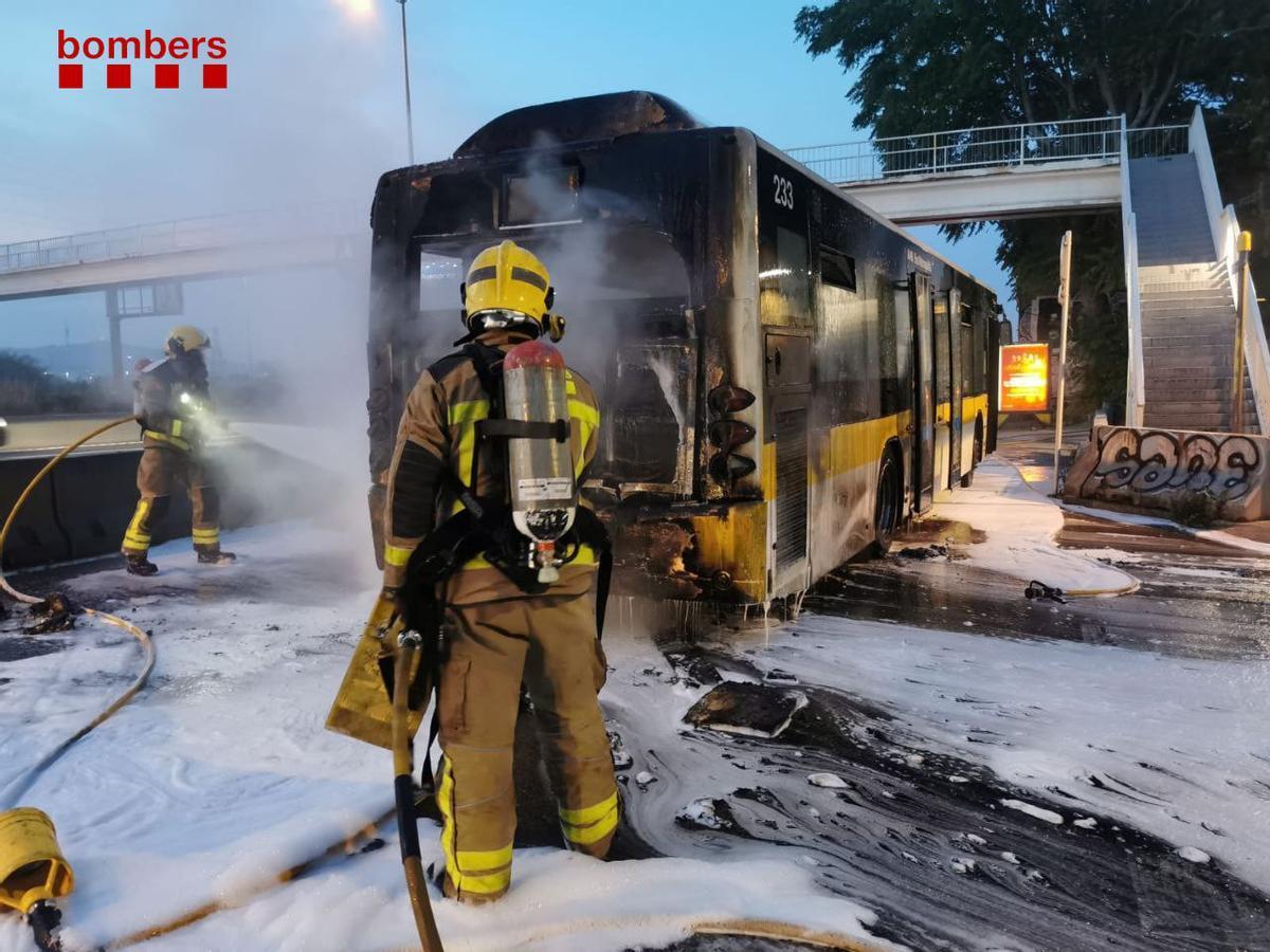 Los bomberos extinguen el incendio en el autobús.