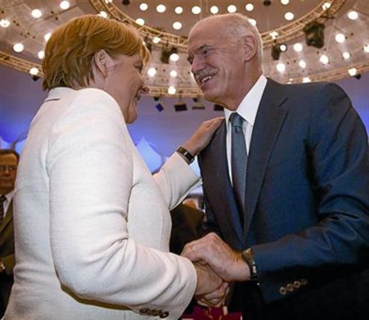 Merkel y Papandreu se saludan, ayer, durante la reunión de la Federación Alemana de Industria, en Berlín.