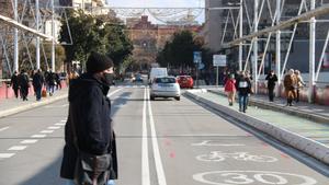 Un viandante cruza una calle de Terrassa en la que se ha pintado la limitación de 30 km/h junto a las siluetas de bicicleta y patinete