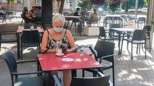 Una mujer toma un café en una terraza de la plaza de Ricard Vinyes de Lleida, este jueves.