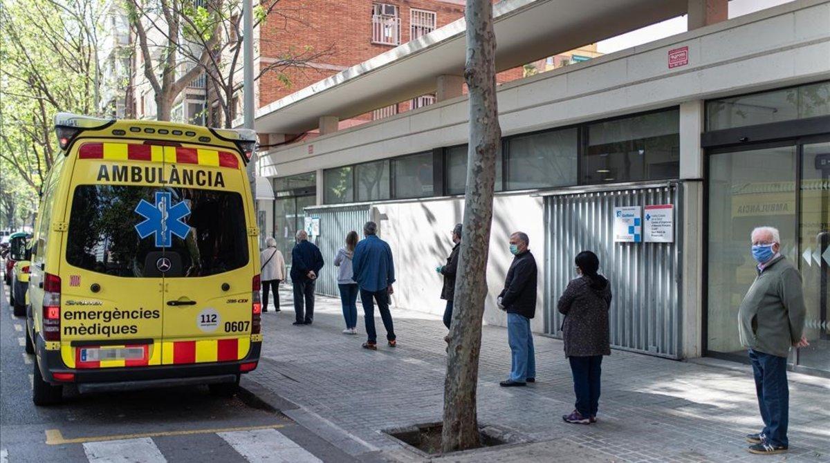 Varias personas hacen cola respetando la distancia de seguridad para entrar en un ambulatorio, junto a una ambulancia del SEM, en Barcelona.