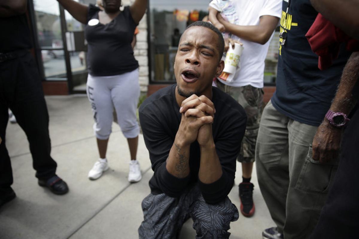 Un hombre reza mientras la policía dispersa a los manifestantes en Ferguson tras el asesinato de Michael Brown.