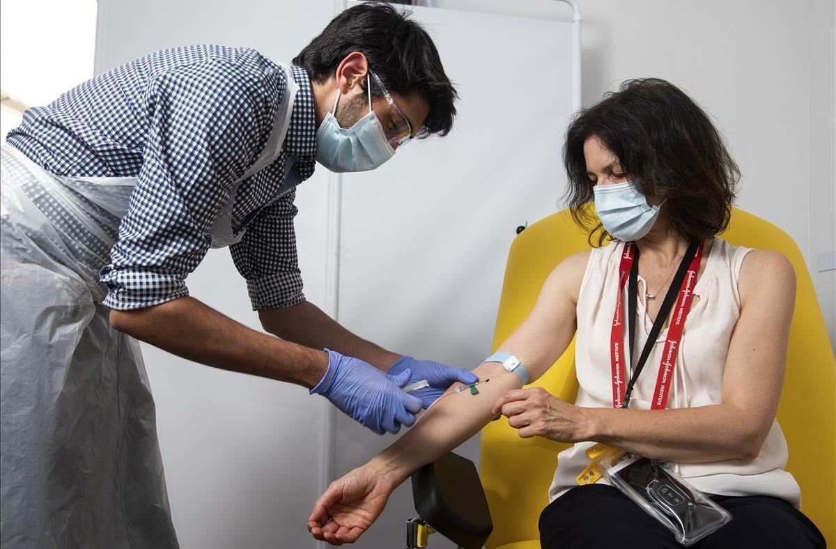 Un doctor extrae una muestra de sangre de una paciente que participa en los ensayos clínicos de la vacuna de Oxford contra el coronavirus SARS-CoV-2, responsable de la enfermedad covid-19.