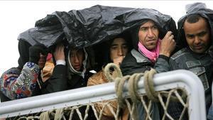 Un grupo de refugiados se protege de la lluviaantes de desembarcar enPorto Empedocle, en el sur de Sicilia.
