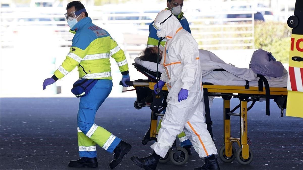 Enfermeros trasladan a una mujera las Urgencias de un hospital de Madrid.