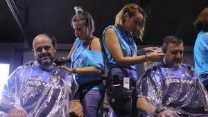 Dos peluqueras cortan el pelo a policías de Terrassa en una acción solidaria con el cáncer infantil.