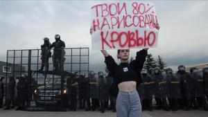 Una joven sostiene en una pancarta en la que está escrito Tu 80% está manchado de sangre, en relación al porcentaje obtenido por Lukashenko en las elecciones presidenciales, calificada de fraudulentas por la oposición.