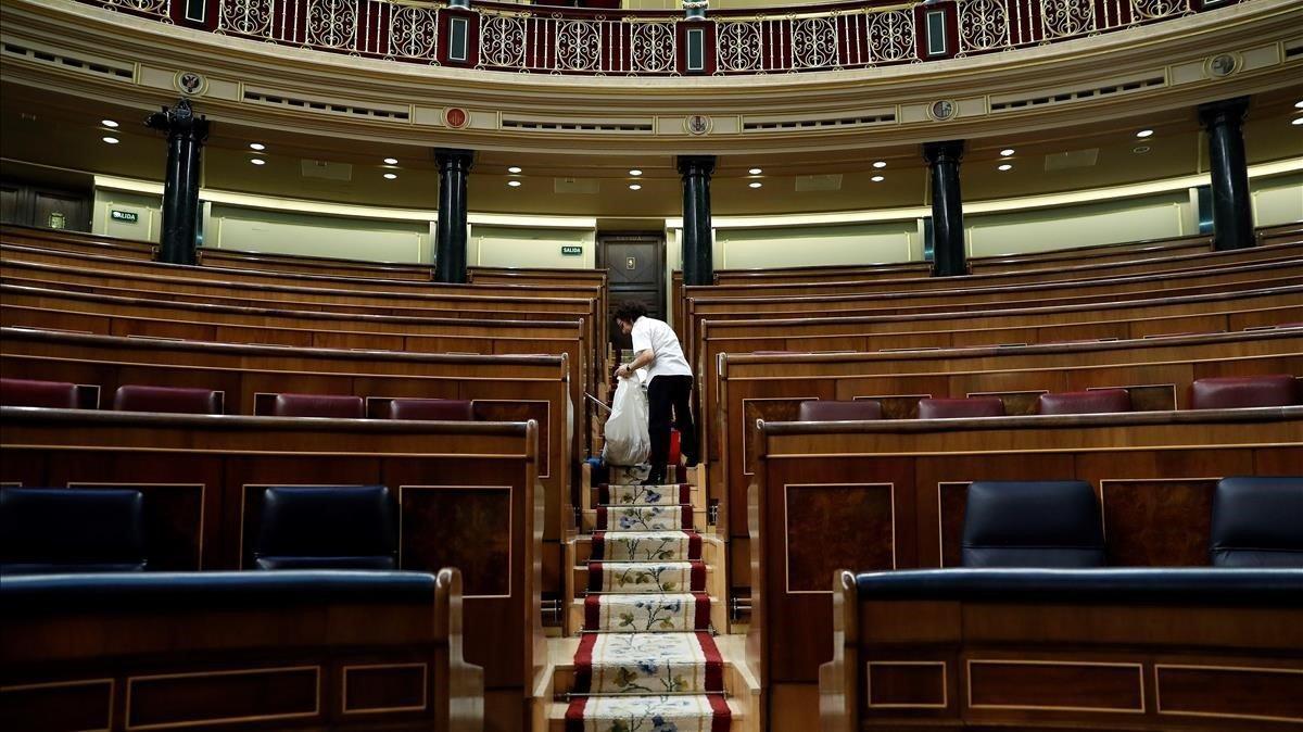 Labores de limpieza en el hemiciclo del Congreso de los Diputados, tras quedarse vacío el pasado 28 de febrero.
