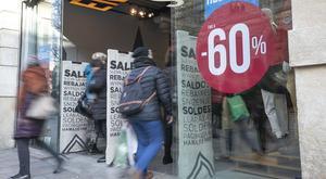 Carteles de rebajas en una tienda de moda del Portal de l'Àngel de Barcelona, este sábado.