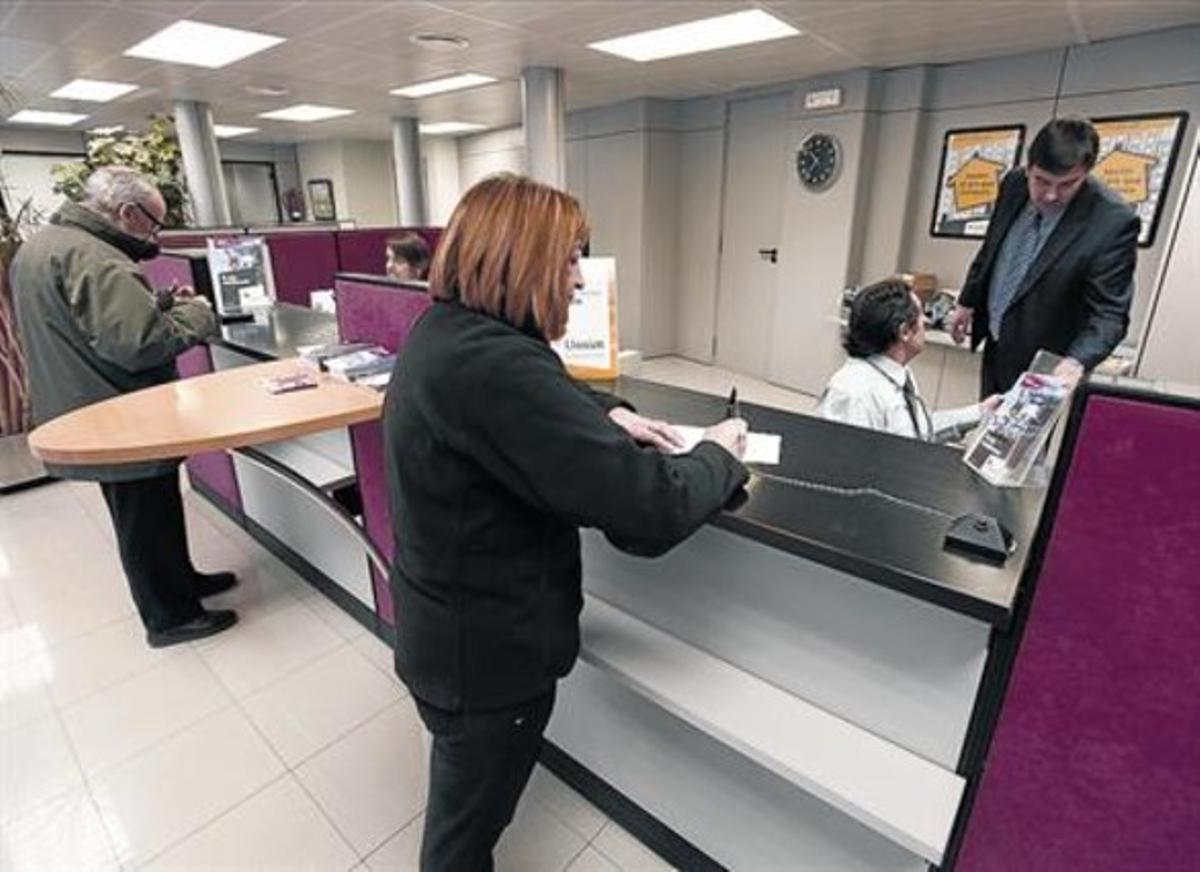 Una clienta realiza una gestión en una oficina bancaria.