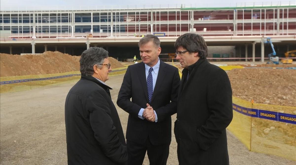 El president de la Generalitat, Carles Puigdemont; el director general de opreciones de Amazon, Fred Pattje (centro); y el alcalde de El Prat, Lluís Tejedor (izquierda), en la visita a las obras del centro logístico.