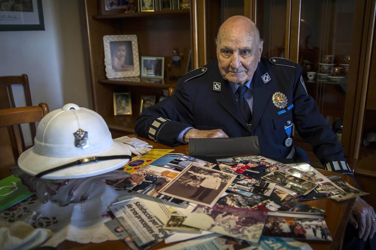 Josep Sánchez, con su casco salacot de la Guardia Urbana y frente a una mesa repleta de recuerdos.
