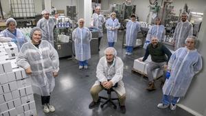 Pere Periche (sin bata) con su equipo de producción y almacenaje, en la fábrica de geles y champús de Periche Profesional, en Montcada i Reixac.