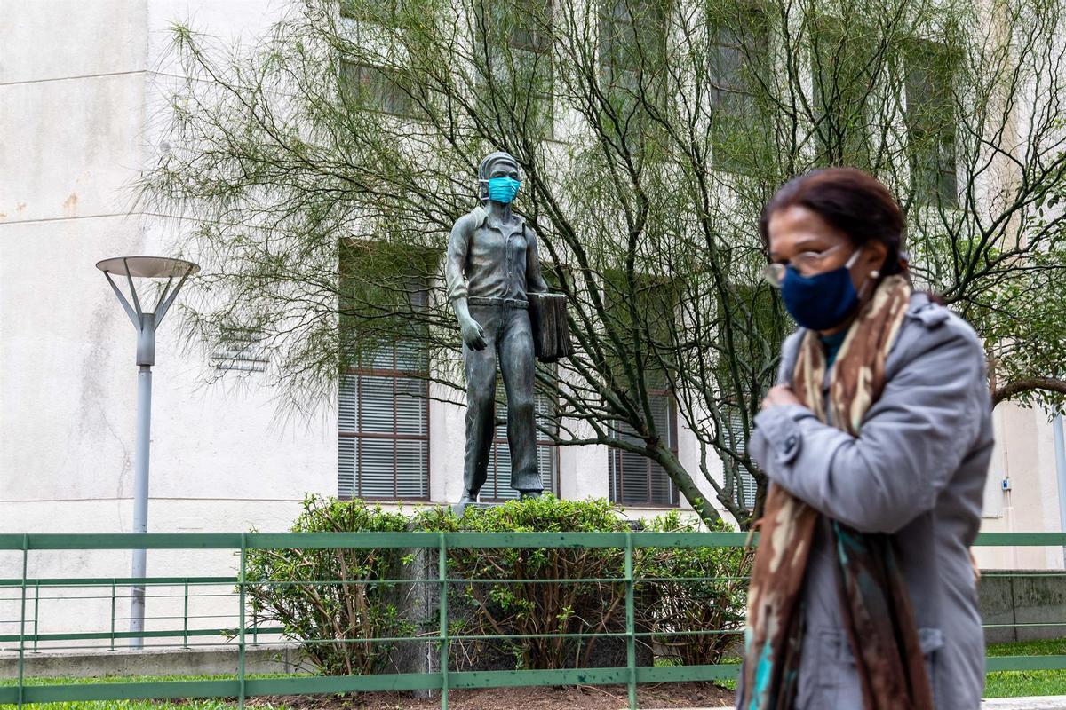 Una mujer pasa frente a una estatua con mascarilla en Montevideo, acción promovida por el Gobierno para fomentar el uso de mascarilla.