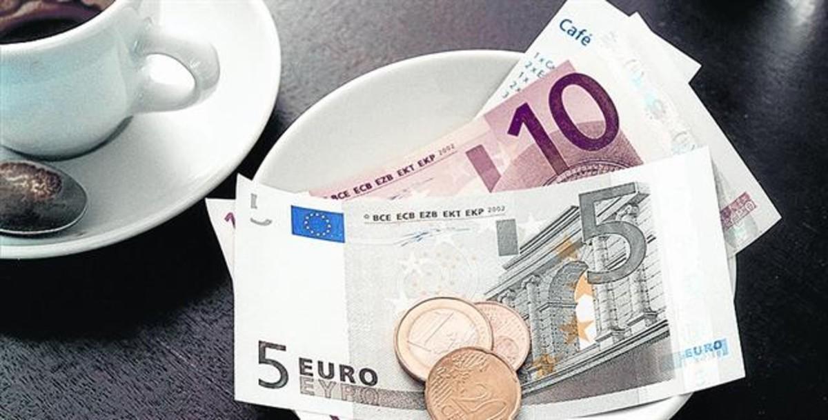 Complementarios 8Cambio en billetes y monedas en la mesa de una cafetería tras una consumición.