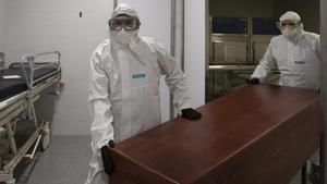 Los funerarios se visten con un EPI para trasladar un difunto fallecido de coronavirus Covid-19 desde la morgue del Hospital de Mataró hasta el tanatorio