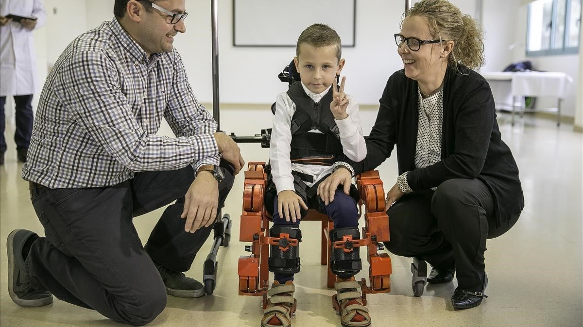 El pequeño Jens, con un exoesqueleto, acompañado de sus padres, Mette Kruse y Àngel Boj, en el Hospital Sant Joan de Déu.