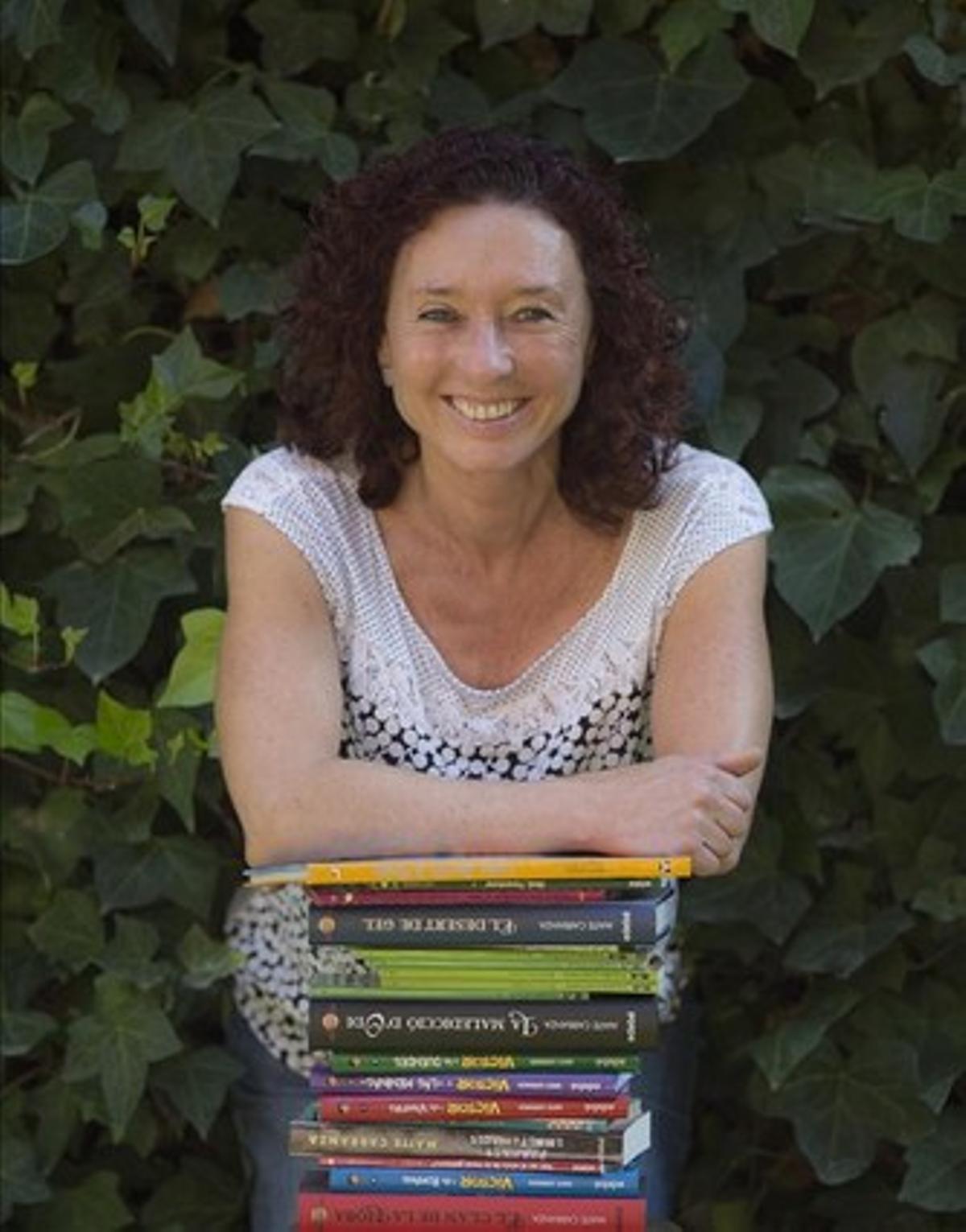 Maite Carranza, en el patio de su casa, apoyada en sus libros, que se han traducido a más de 20 lenguas.