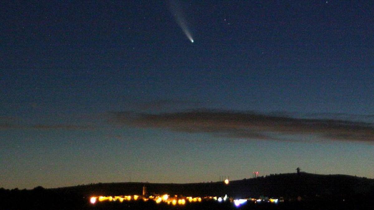 El cometa Neowise, fotografiado encima de un centro habitado fuertemente iluminado.