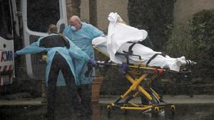 Un equipo de sanitarios traslada a un paciente, en medio de una fuerte lluvia, en Kirkland, en el estado de Washington.
