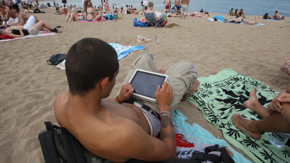 Un hombre consulta su tableta en la playa de Barcelona.