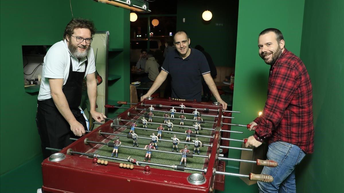 Rafa Peña, Juanlu Pérez (en el centro) y Biel Gavaldà, le dan al futbolín en el Bar Torpedo.