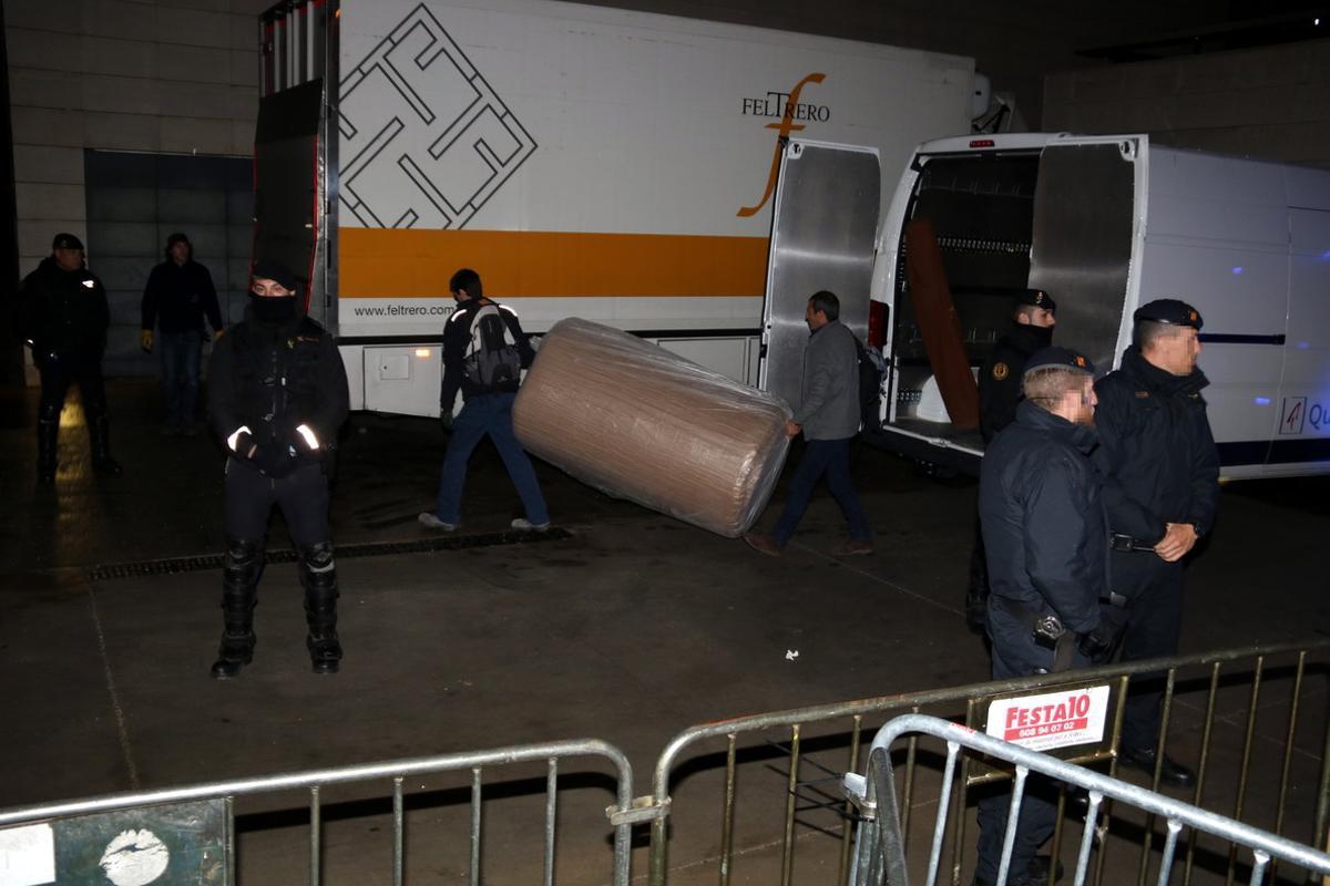 Trabajadores de la empresa encargada del traslado de las obras de arte descargan cajas ante el Museu de Lleida, esta madrugada.