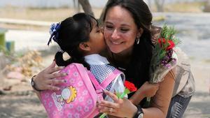 Una maestra recibe un beso de una niña a la entrada de un colegio.
