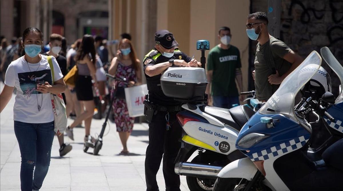 Un policía extiende una multa a un ciudadano en una calle de Barcelona, el verano pasado.