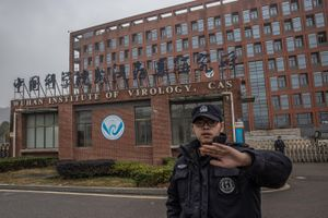 Un guardia de seguridad impide a los fotógrafos acercarse al Instituto de Virología de Wuhan.
