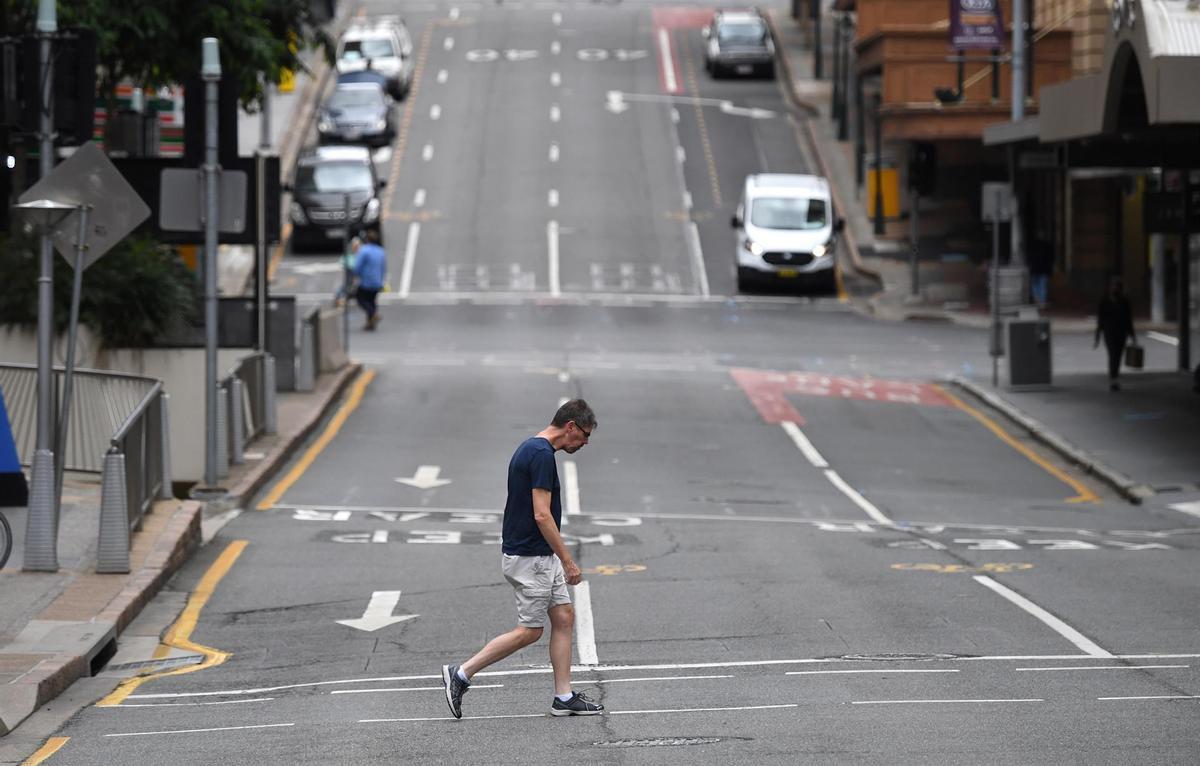 Un hombre cruza una calle casi vacía en Brisbane.