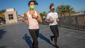 Dos chicas corren con mascarilla por el paseo Marítim de Barcelona.