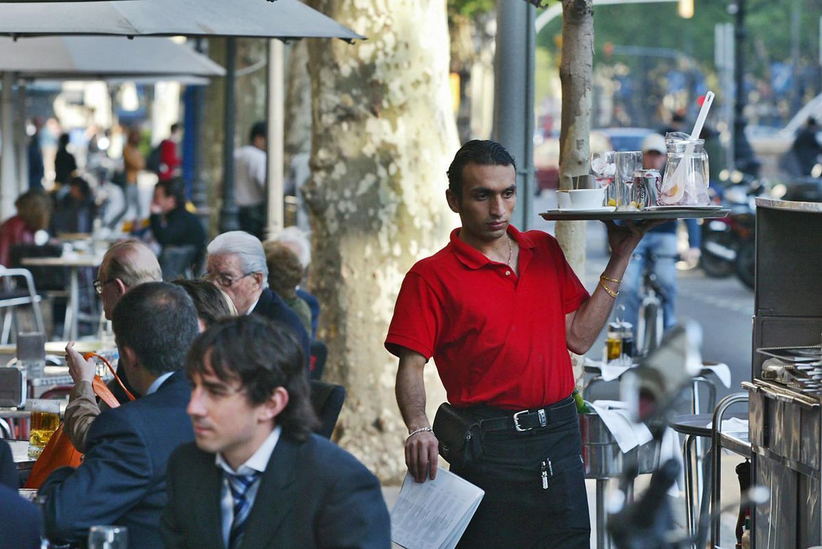 Un camarero trabajando en una terraza de un bar del Passeig de Gràcia de Barcelona.