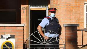 Un mosso d'Esquadra custodia la puerta de una vivienda ocupada en Pallejà, el pasado 19 de agosto.
