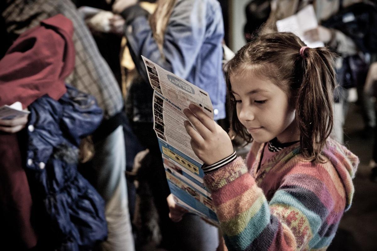 Una niña repasa con atención el programa de El Meu Primer Festival.