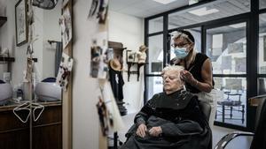 Una mujer, en la peluquería del pueblo que acoge a personas con alzhéimer.