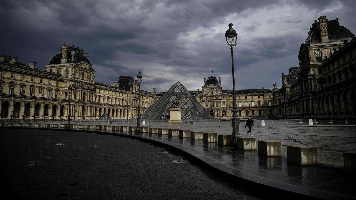 Una mujer pasa junto a la pirámide de cristal frente al Louvre en medio del cierre nacional debido al coronavirus.