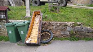 Ataúd abandonado junto a la basura.