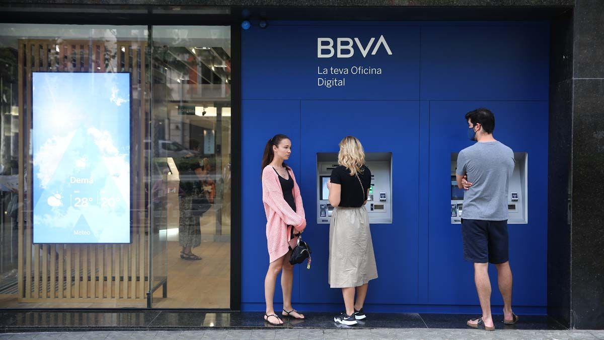Gente operando en un cajero de BBVA en Barcelona.