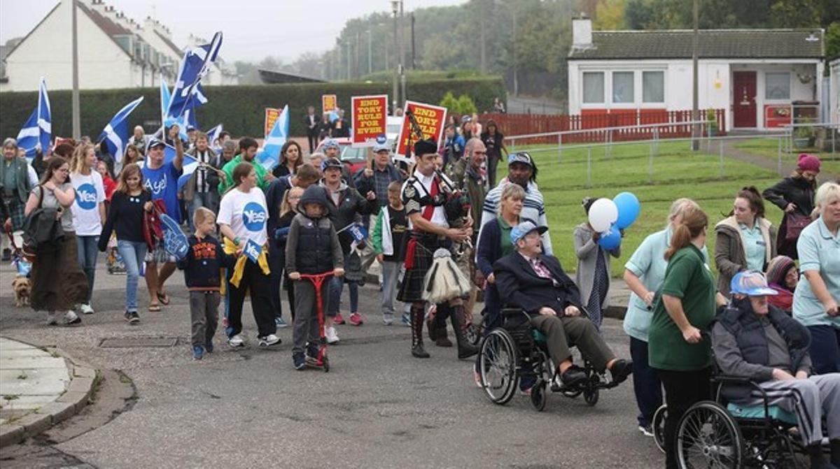Grups de residents es dirigeixen a votar, a Edimburg, aquest matí.