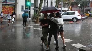 Paraguas bajo la lluvia esta tarde en la ciudad.