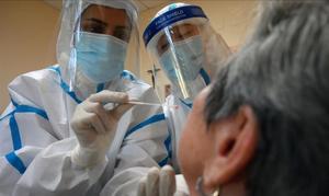 Trabajadores sanitarios hacen un test de coronavirus a uno de los ingresados en la residencia de ancianos Sant Miquel, en Barcelona.
