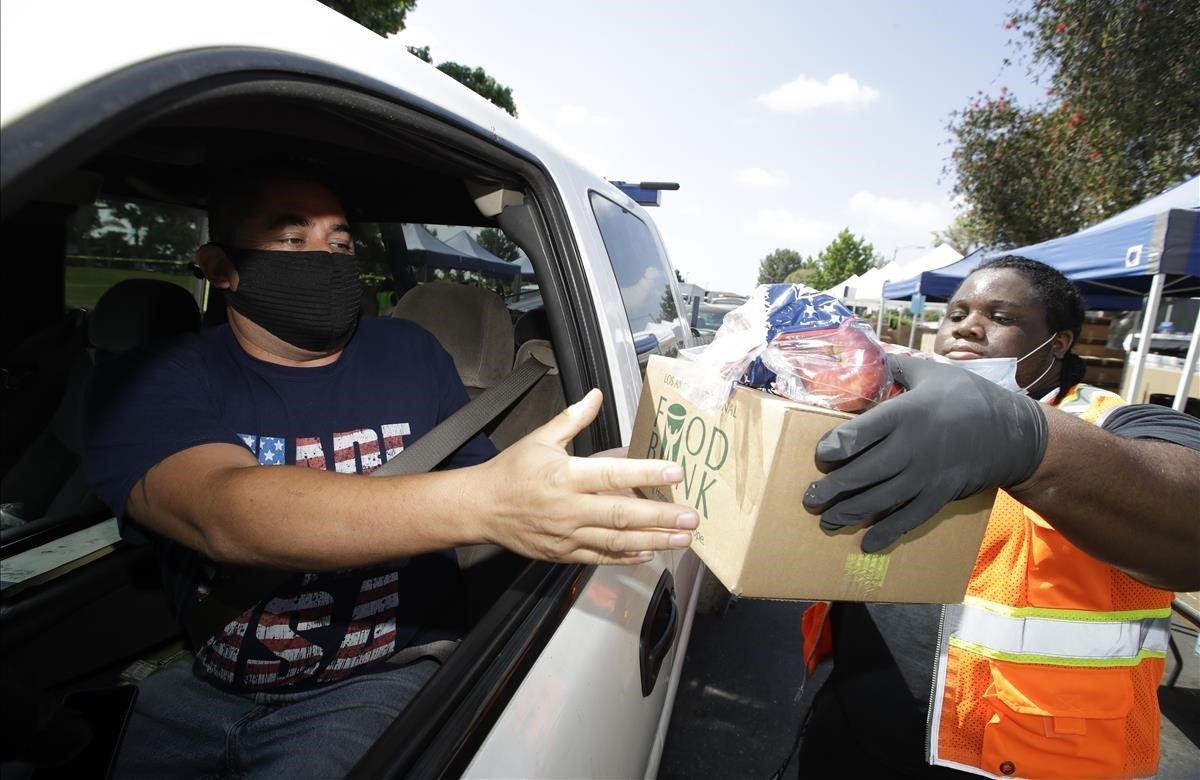 Jeremiah Washington, distribuye alimentos. Las cifras de desempleo continúan aumentando y más estadounidenses recurren a la distribución de alimentos en medio de la pandemia.