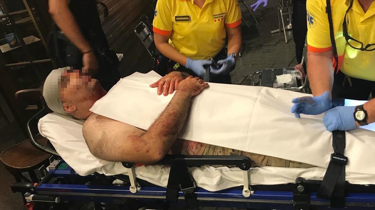 El turista agredido por un mantero es trasladado en camilla al Hospital Clínic