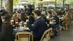 Customers sit on terraces, in Paris, on May 19, 2021 as cafes, restaurants and other businesses re-opened as part of an easing of the nationwide lockdown due to the Covid-19 pandemic. - The French made their way back to cafes and prepared long-awaited visits to cinemas and museums as the country loosened restrictions in a return to semi-normality after over six months of Covid-19 curbs.Cafes and restaurants with terraces or rooftop gardens can now offer outdoor dining, under the second phase of a lockdown-lifting plan that should culminate in a full reopening of the economy on June 30. (Photo by Bertrand GUAY / AFP)