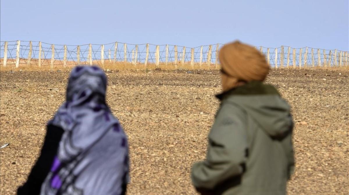 Zghala, una mujer del Sáhara Occidental, mira hacia la valla en el área de Al-Mahbes, mientras acompaña a su hijo de 14 años para mostrarle el muro que separa Marruecos de la zona controlada por el Polisario, el 3 de febrero del 2017.