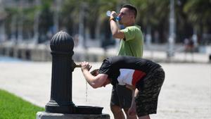 Dos personas se refrescan bajo el sol en el Port Vell